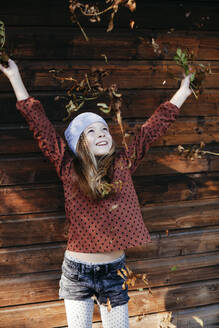 Smiling girl standing in front of a wooden wall with arms outstretched outdoors - HMEF00655