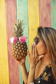 Playful young woman talking to pineapple with sunglasses on summer patio - HEROF39177