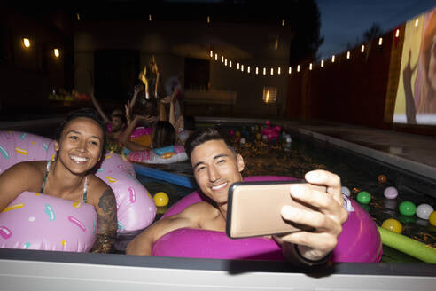 Happy, carefree young couple with inflatable rings taking selfie with camera phone in summer swimming pool - HEROF39219