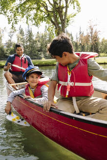 Young boy playing with toy boat in canoe with brother and father - HEROF39261
