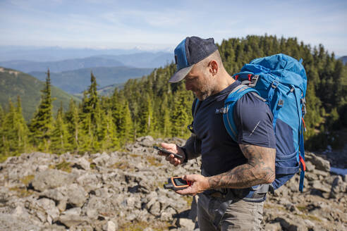 Hiker pairs his phone and GPS to navigate in the backcountry. - CAVF65751
