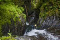 High angle view man rappelling beside waterfall in Frost Creek Canyon. - CAVF65778