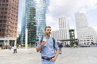 Man in the city holding a cup of coffee, Berlin, Germany - WPEF02063