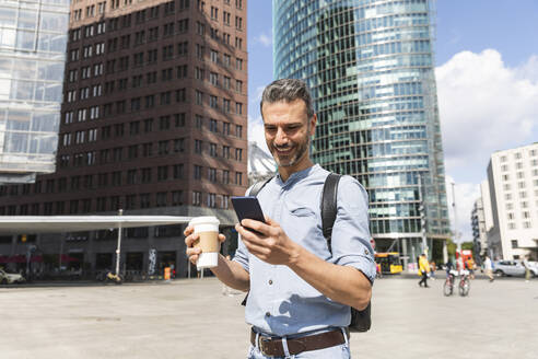Smiling businessman looking at the smartphone in the city, Berlin, Germany - WPEF02066