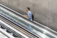 Businessman walking up escalator in the city - WPEF02078