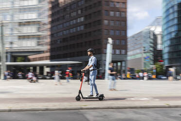 Businessman riding e-scooter on the pavement in the city, Berlin, Germany - WPEF02084