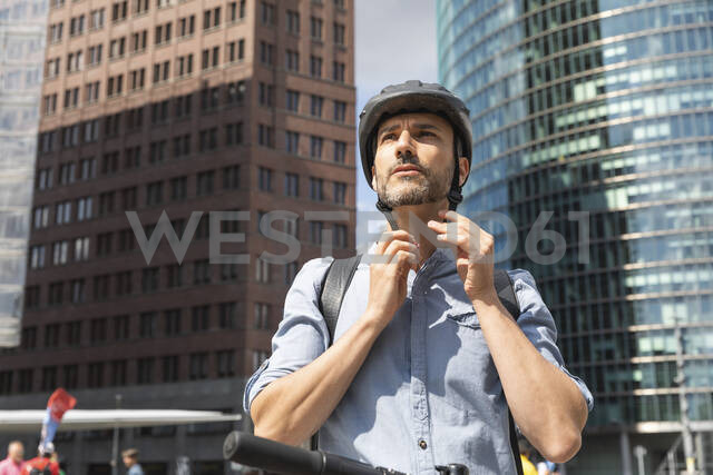 Man fastening the helmet before riding on electric scooter, Berlin, Germany - WPEF02087 - William Perugini/Westend61