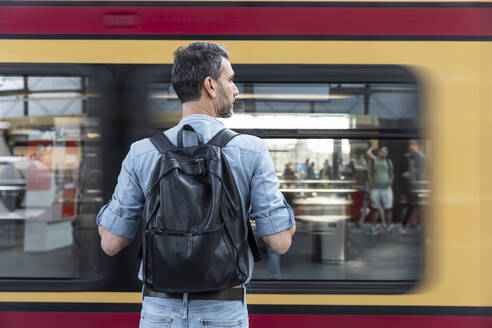 Rear view of man with backpack at the station platform while train coming in - WPEF02096
