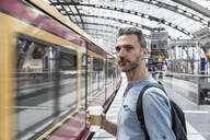 Man with takeaway coffee at the station while train coming in - WPEF02099