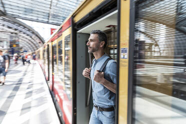 Man getting out of the train at the station platform - WPEF02102