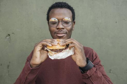 Young man eating cheeseburger, with eyes closed - VPIF01636