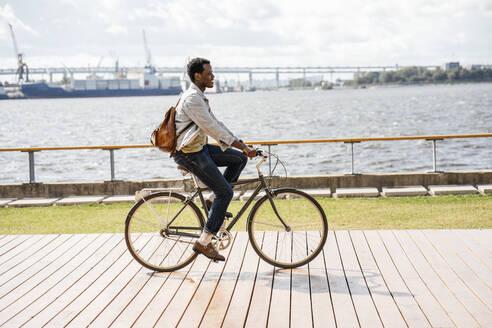 Young man riding bicycle at the sea - VPIF01684