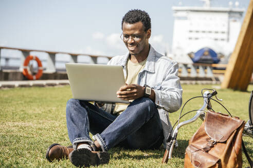 Young man sitting on grass, using laptop - VPIF01696