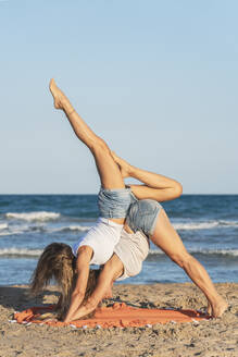 Two women praticing Acro Yoga on the beach - DLTSF00261