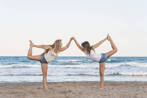 Two women praticing Acro Yoga on the beach - DLTSF00264