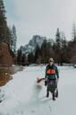 Man dragging kayak across snow, Yosemite Village, California, United States - ISF22565