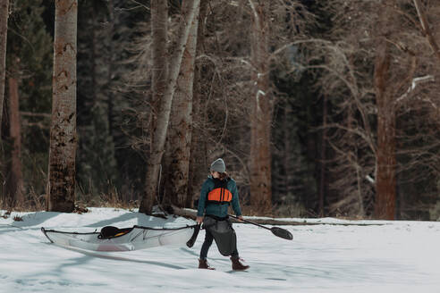 Man dragging kayak across snow, Yosemite Village, California, United States - ISF22571