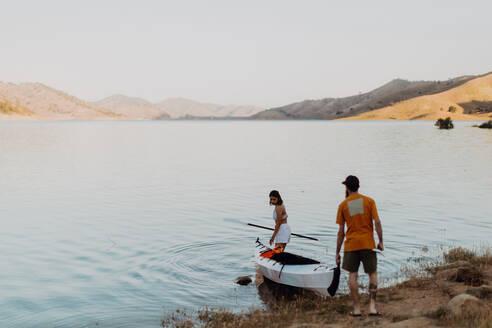 Couple carrying kayak to lake, Kaweah, California, United States - ISF22580