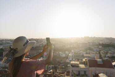 Woman taking a smartphone picture of the city panorama, Lisbon, Portugal - AHSF01005