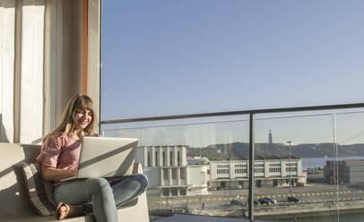 Woman using laptop on a sunny terrace, Lisbon, Portugal - AHSF01008