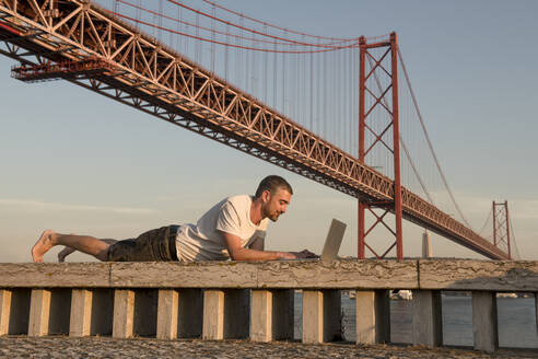 Man using laptop at 25th of April Bridge in Lisbon, Portugal - AHSF01014