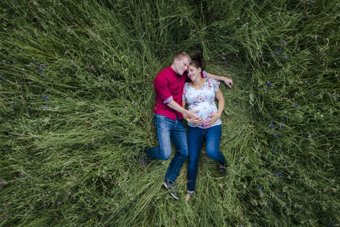 Pregnant woman and man holding baby belly, lying on meadow - HMEF00661