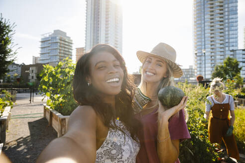Personal perspective young women friends taking selfie in sunny, urban community garden - HEROF39425