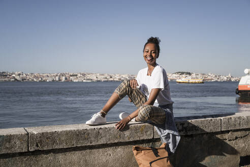 Portrait of happy young woman sitting on a wall at the waterfront, Lisbon, Portugal - UUF19066