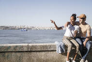 Happy young couple sitting on a wall at the waterfront, Lisbon, Portugal - UUF19072