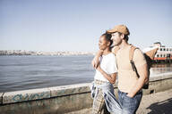 Young couple walking at the waterfront, Lisbon, Portugal - UUF19078