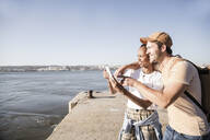 Young couple using cell phone on pier at the waterfront, Lisbon, Portugal - UUF19102