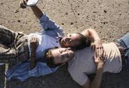 Happy young couple lying on concrete floor taking a selfie - UUF19111