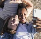 Happy young couple lying on concrete floor taking a selfie - UUF19114