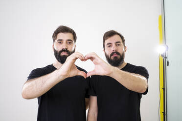 Gay couple forming heart shape with hands and fingers - AFVF04146