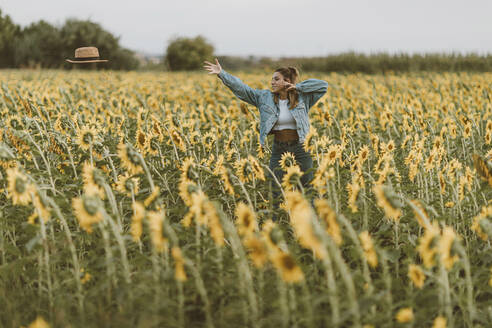Young woman with blue denim jacket throwing a hat in a field of sunflowers - OCAF00428