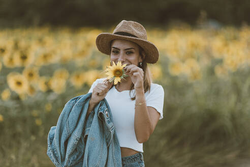 Portrait of young woman with blue denim jacket and hat in a field of sunflowers - OCAF00434
