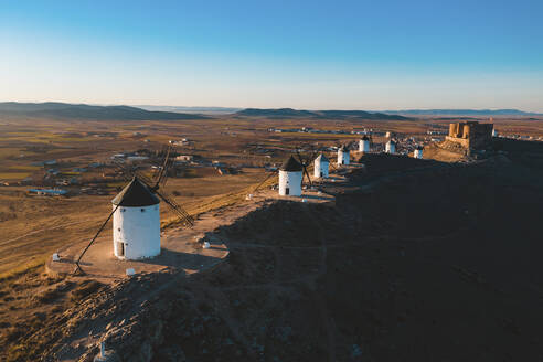 Spain, Province of Toledo, Consuegra, Row of old windmills standing on top of brown hill - WPEF02108