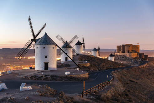 Spain, Province of Toledo, Consuegra, Road along row of old windmills standing on top of hill - WPEF02111