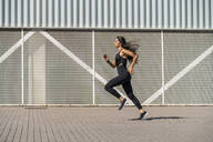 Young female jogger running in front of a wall - MTBF00035