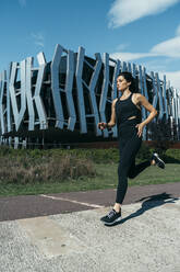 Young woman jogging on a way, modern building in the background - MTBF00041