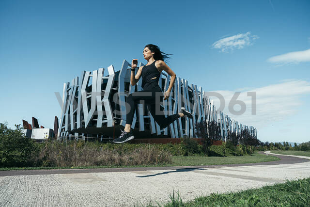 Young female jogger on a way in front of a modern building - MTBF00044 - Mikel Taboada/Westend61