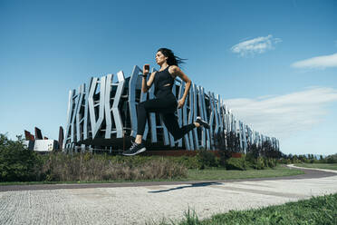 Young female jogger on a way in front of a modern building - MTBF00044