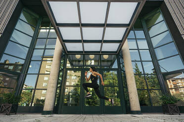 Young female jogger jumping in front of a building entrance - MTBF00047