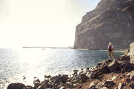 Rear view of hiker at the beach, Valle Gran Grey, La Gomera, Canary Islands, Spain - MAMF00904