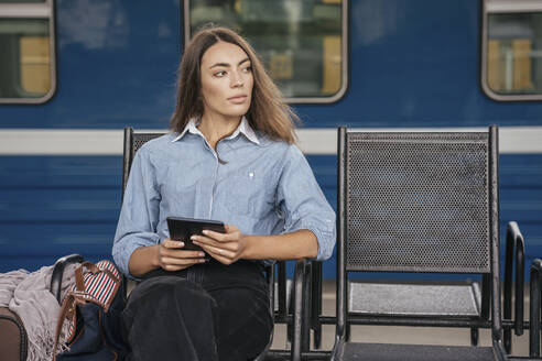Young female traveller waiting on station, using e-book - VPIF01732