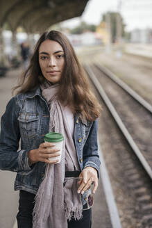 Young female traveller with coffee to go on train station - VPIF01741