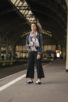 Young female traveller standing with coffee to go on the platform - VPIF01744