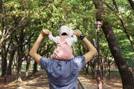 Father walking in a park with baby girl on his shoulders - GEMF03234