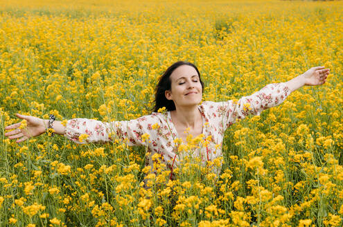Portrait of happy woman with eyes closed and arms outstretched in a rape field - GEMF03237