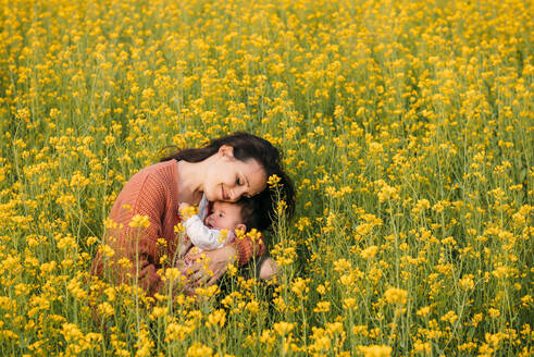 Happy mother cuddling with baby girl in a rape field - GEMF03240